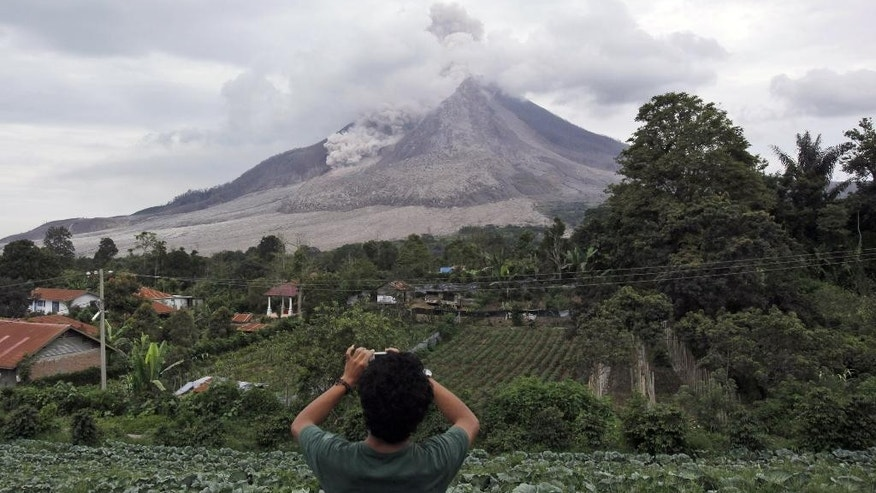 FILE - In this Friday, June 5, 2015, file photo, an Indonesian man takes pictures of Mount Sinabung as it releases volcanic materials in Tiga Serangkai, North Sumatra, Indonesia. Indonesia has raised the alert status of the volcano in the western part of the country to the highest level following a sharp increase in activity this week. (AP Photo/Binsar Bakkara, File)