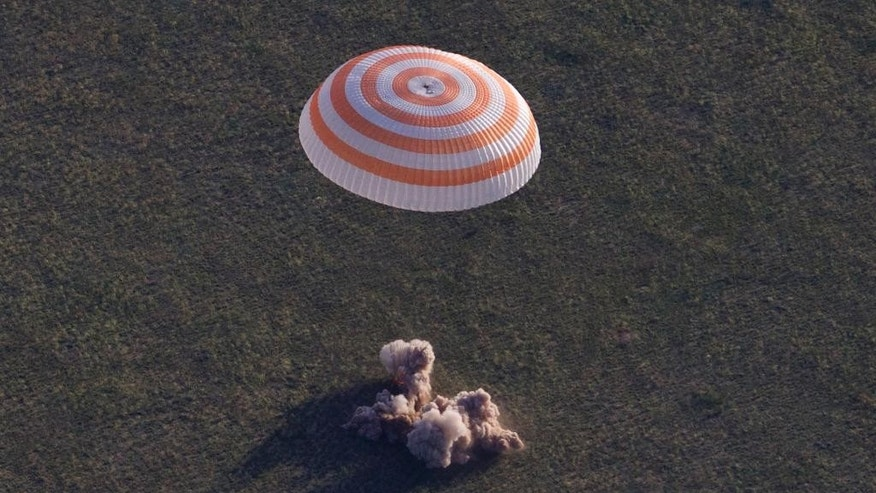 Russian Soyuz TMA-15M space capsule carrying the International Space Station (ISS) crew of Russian cosmonaut Anton Shkaplerov, U.S. astronaut Terry Virts and Italian astronaut Samantha Cristoforetti lands in a remote area outside the town of Dzhezkazgan, Kazakhstan, on Thursday, June 11, 2015. The three-person crew from the International Space Station landed safely in the steppes of Kazakhstan on Thursday after a longer-than-expected orbital stint. (AP Photo/Ivan Sekretarev, pool)