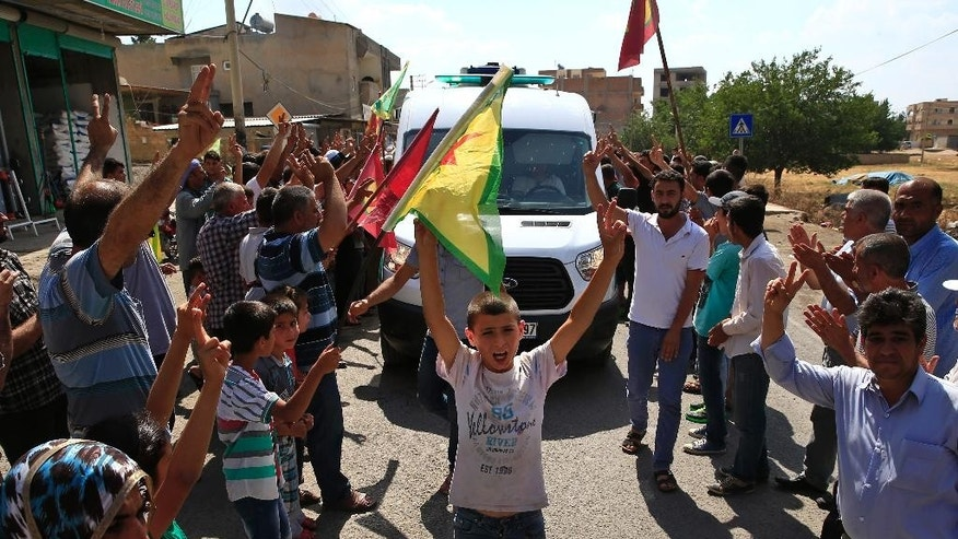 Kurdish people waving flags flash the V-sign and applaud while lining the road, as the convoy carrying the body of Hanim Dabaan, killed in fighting with the militants of the Islamic State group in Kobani, Syria, is driven by through Suruc, on the Turkey-Syria border, Thursday, June 11, 2015. Keith Broomfield, 20 from Massachusetts, died June 3 in battle in a Syrian village near Kobani, making him likely the first U.S. citizen to die fighting alongside  Kurds against the Islamic State group. (AP Photo/Lefteris Pitarakis)