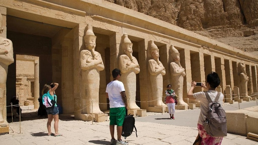 Visitors tour the Hatshepsut Temple in Deir el-Bahari on the west bank of the Nile River at Luxor, Egypt, Thursday, June 11, 2015. Militants tried to attack the ancient temple of Karnak in southern Egypt on Wednesday, with a suicide bomber blowing himself up and two gunmen battling police. No sightseers were hurt in the thwarted assault. (AP Photo/Hassan Ammar)