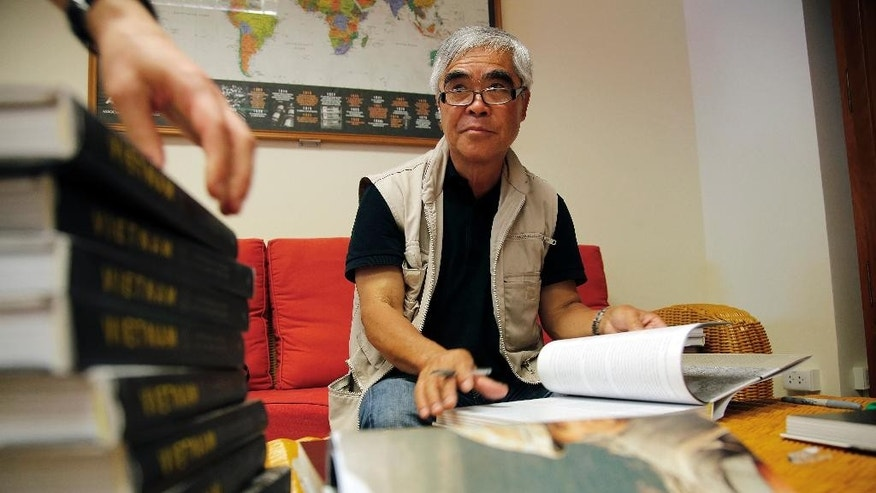 """In this Wednesday, June 10, 2015, photograph, Pulitzer Prize winning photographer Nick Ut signs copies of the book """"Vietnam The Real War"""" which features his iconic 'Napalm girl' photo, in Hanoi, Vietnam ahead of the opening of an exhibit of AP's wartime photographs in Hanoi. This month marks the 20th anniversary of restored diplomatic ties between the U.S. and Vietnam. (AP Photo/Wong Maye-E)"""