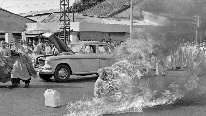 "FILE - In this June 11, 1963, file photo, Thich Quang Duc, a Buddhist monk, sets himself on fire and burns to death at a highway intersection in Saigon, Vietnam. Forty years after the war ended, ""Vietnam: The Real War,"" a collection of 58 photographs taken by the AP opens to the public Friday, June 12, 2015, in Hanoi, Vietnam. (AP Photo/Malcolm Browne, File)"
