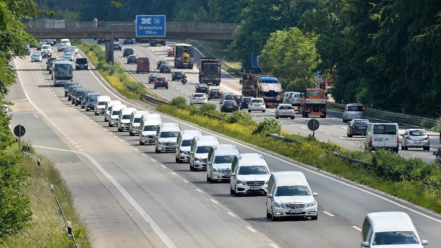 A convoy of hearses drives on the highway in Duisburg, Germany, Wednesday, June 10, 2015, taking home 16 school children who died in the Germanwings plane crash in March. The coffins, that arrived at the airport in Duesseldorf Tuesday evening, are brought to their families in the city of Haltern. (AP Photo/Martin Meissner)