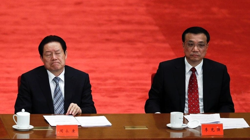 FILE - In this May 4, 2012 file photo, Zhou Yongkang, left, then Chinese Communist Party Politburo Standing Committee member in charge of security, and Li Keqiang, right, then Chinese vice premier and now premier, attend a conference to celebrate the 90th anniversary of the founding of Chinese Communist Youth League at the Great Hall of the People in Beijing. According to China's Xinhua News Agency, Zhou was sentenced to life imprisonment Thursday, June 11, 2015 by a court in Tianjin on charges of receiving bribes, abuse of power, and leaking state secrets following a closed-door trial. (AP Photo/Alexander F. Yuan, File)