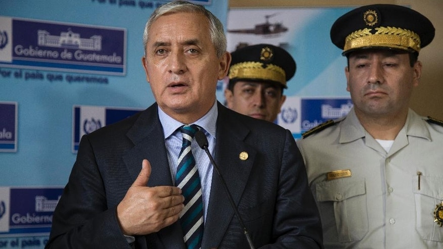Guatemala's President Otto Perez Molina speaks during a press conference accompanied by police chiefs, at the Interior Ministry in Guatemala City, Thursday, June 11, 2015. Guatemala's Supreme Court gave the go-ahead Wednesday for congress to decide whether to remove Perez Molina's immunity from prosecution in a corruption scandal. (AP Photo/Luis Soto)