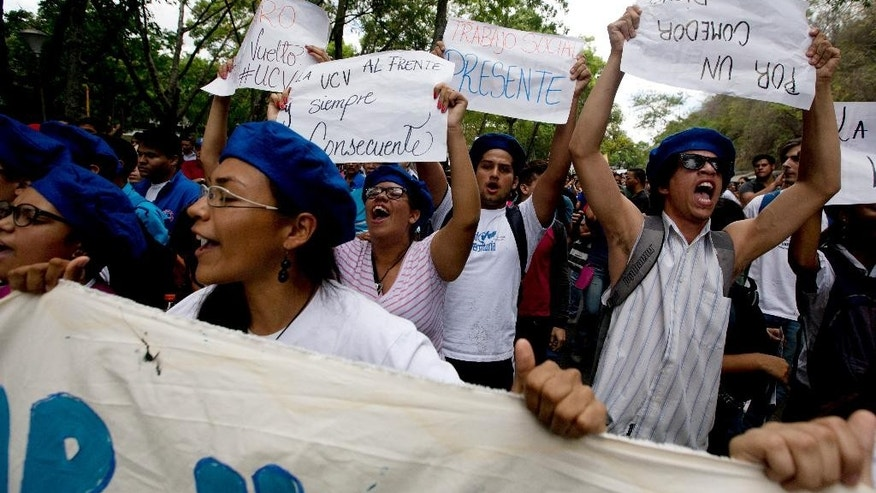 In this Thursday, May 28, 2015 photo, students and teachers shout slogans demanding better salaries during a protest at Venezuela's Central University, UCV, in Caracas, Venezuela. Hundreds of professors have given up their posts in recent years, and the pace is accelerating, according to the teachers' union. (AP Photo/Fernando Llano)