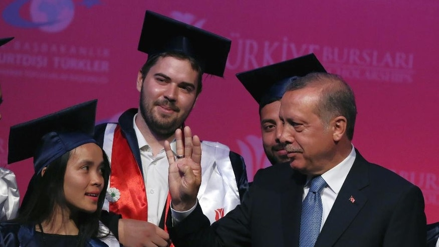 Turkey's President Recep Tayyip Erdogan makes the sign of the Rabaah movement in Egypt during a graduation ceremony for foreign students in Ankara, Turkey, Thursday, June 11, 2015. In his first televised appearance since his ruling party lost its parliamentary majority, Erdogan has asked all Turkish political parties to put aside their differences and rapidly form a new government. (AP Photo/Burhan Ozbilici)