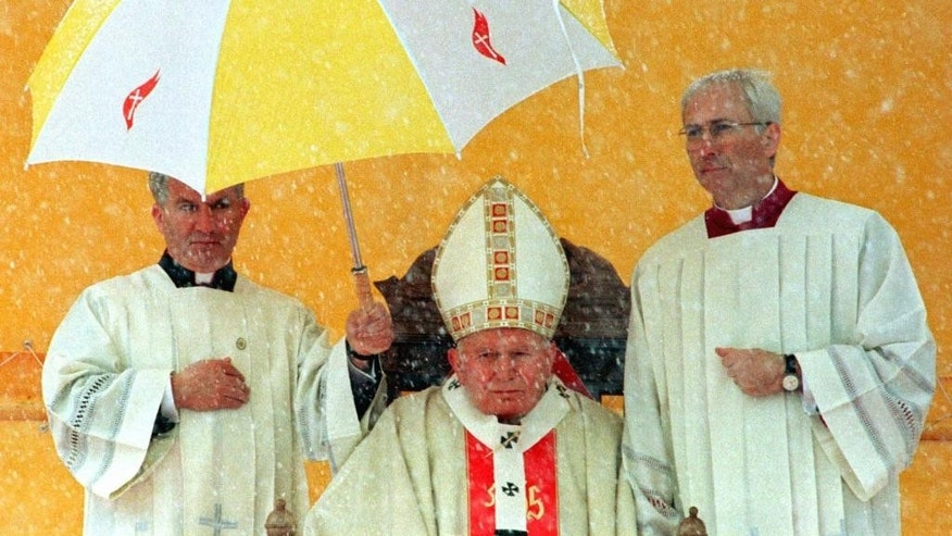 FILE - In this Sunday April 13, 1997 file photo clergymen hold an umbrella over Pope John Paul II during a snow storm as the Holy Father celebrates a Mass for tens of thousands of Bosnian worshippers at Sarajevo Kosevo Stadium. Anxiety has so gripped American conservatives over Pope Francis' upcoming encyclical on the environment that you might think a pope had never before blamed fossil fuels for global warming. Or accused energy companies of hoarding the Earth's resources at the expense of the poor. Or urged the rich to consume less and share more. (AP Photo/Jacqueline Arzt, file)