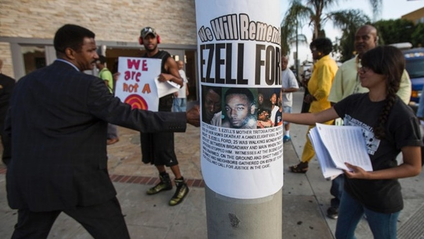 "FILE - In this Aug. 19, 2014, file photo, a poster reads ""We Will Remember Ezell Ford"" in front of Paradise Baptist Church before a community forum in Los Angeles, to discuss the Aug. 11 police shooting of Ezell Ford. The Los Angeles Police Commission vote Tuesday, June 9, 2015, was unanimous involving both officers, finding that the senior officer was not justified in the August shooting death of Ford, but his junior partner was justified. (AP Photo/Ringo H.W. Chiu, File)"