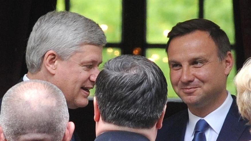 Canadian Prime Minister Stephen Harper, left, arrives for a meeting with Poland's President-elect Andrzej Duda, right,  in Warsaw, Poland, Tuesday, June 9, 2015. (AP Photo/Alik Keplicz)