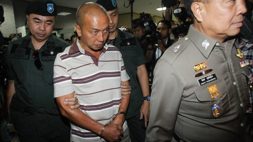 Montri Sotangkur, center, a senior palace official under former Princess Srirasmi, escorted by Thai policemen, arrives at the police headquarters in Bangkok, Thailand, Thursday, June 11, 2015. The official was accused of abuse of authority by claiming royal connections in demanding positions with two of Thailand's influential private enterprises. He faces up to 20 years in prison from four arrest warrants. (AP Photo/Sakchai Lalit)