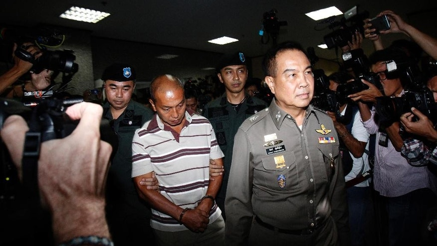 Montri Sotangkur, center, a senior palace official under former Princess Srirasmi, is escorted by Thai policemen as he arrives at the police headquarters in Bangkok, Thailand, Thursday, June 11, 2015. The official was accused of abuse of authority by claiming royal connections in demanding positions with two of Thailand's influential private enterprises. He faces up to 20 years in prison from four arrest warrants. (AP Photo/Sakchai Lalit)