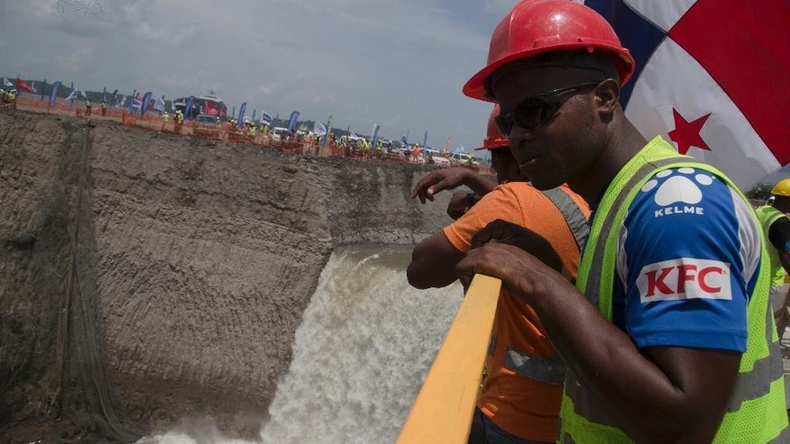 A canal worker looks over a railing as water from the Atlantic begins to flood the Gatun flood chambers that will provide water to the new set of locks in the Atlantic side of the Panama Canal in Colon, Panama, Thursday, June 11, 2015.  Water began flooding into an expanded section of the Panama Canal as engineers begin testing new locks. It's a key step in a project that will affect trade across the world. (AP Photo/Tito Herrera)