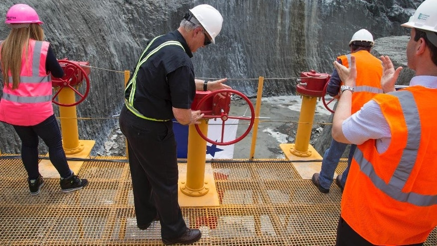 The head of the Panama Canal Authority Jorge Quijano, center, opens the main valve to flood the Gatun flood chambers that will provide water to the new set of locks in the Atlantic side of the Panama Canal in Colon, Panama, Thursday, June 11, 2015.  Water began flooding into an expanded section of the Panama Canal as engineers begin testing new locks. It's a key step in a project that will affect trade across the world. (AP Photo/Tito Herrera)