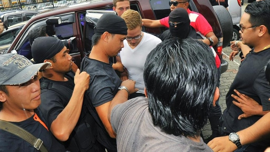 Dutch national Dylan Snel, in white shirt, center, is escorted by police as he arrives at court in Kota Kinabalu, in eastern Sabah state on Borneo island, Malaysia, Friday, June 12, 2015. Snel was among 10 people who stripped naked and took photos on Mount Kinabalu on May 30. A local official has said the foreigners' behavior caused an earthquake near the mountain last Friday that killed 18 climbers. (AP Photo/Syaradik Babuca)