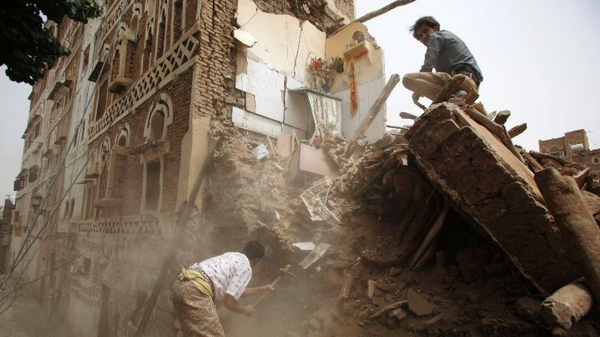 A man searches for survivors under the rubble of houses destroyed by Saudi airstrikes in the old city of Sanaa, Yemen, Friday, June 12, 2015. (AP Photo/Hani Mohammed)