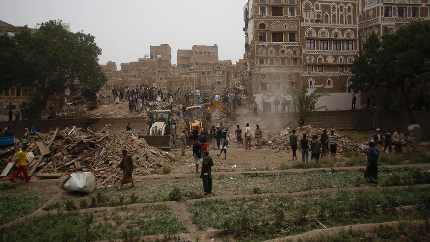 People search for survivors under the rubble of houses destroyed by Saudi airstrikes in the old city of Sanaa, Yemen, Friday, June 12, 2015. (AP Photo/Hani Mohammed)