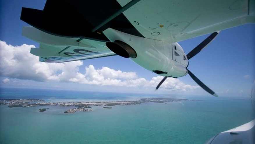 In this, Tuesday, May 19, 2015,  photo, a U.S. Coast Guard HC-144A Ocean Sentry aircraft flies over the Florida Keys. Despite a historic shift in the relationship between the governments on either side of the Florida Straits, the U.S. Coast Guard still plays a deadly hide-and-seek with Cuban migrants on the high seas. (AP Photo/Wilfredo Lee)