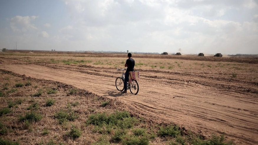 In this Wednesday, June 10, 2015 photo, a Palestinian man on a bicycle watches Israeli bulldozers work along the border between the southern Gaza Strip town of Khan Yunis and Israel. (AP Photo/Khalil Hamra)