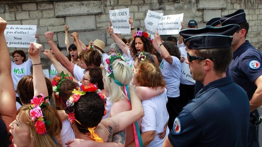 Femen activists chanting slogans and carrying signs reading: Abolition of Prostitution, No Demand No Offer, demonstrate in front of the French National Assembly in Paris, Friday June 12, 2015, asking for the abolition of prostitution. (AP Photo/Remy de la Mauviniere)
