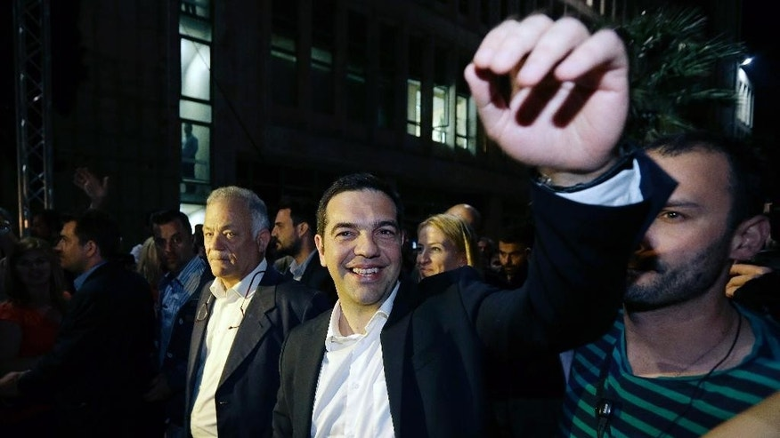 Greece's Prime Minister Alexis Tsipras waves to the crowd at the state broadcaster ERT following its re-launch after two years in Athens on Thursday, June 11, 2015. Greece's public television has resumed operations under its old ERT name, and is proposing to rehire all staff fired in a cost-cutting as International creditors sent Tsipras home from a summit Thursday with a clear message: swiftly tone down your demands in the bailout talks over the next week or face financial ruin. (AP Photo/Thanassis Stavrakis)