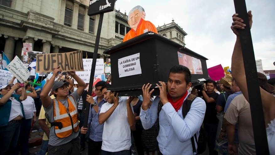 In this Saturday, May 30, 2015 photo, protesters carry a fake coffin with a effigy of Guatemalan President Otto Perez Molina during a protest  to demand his resignation in Guatemala City, Saturday, May 30, 2015. Angered by recent revelations of multimillion-dollar corruption scandals and emboldened by the jailing of dozens of suspects and the resignation of the vice president, the protesters show no sign of letting up. (AP Photo/Moises Castillo)