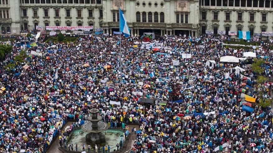 In this May 16, 2015 photo, protesters gather outside the National Palace to demand the resignation of Guatemalan President Otto Perez Molina in Guatemala City. Every Saturday for nearly two months, Constitution Square outside Guatemala City's National Palace has overflowed with thousands of protesters demanding an end to corruption and the resignation of the President.  (AP Photo/Moises Castillo)