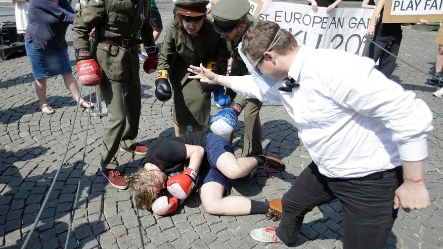 Human rights activists, dressed as policemen and athletes, stage a happening to advert to  what they say, violation of human rights in Azerbaijan, host country of Baku 2015 European Games, in Prague, Czech Republic, Friday, June 12, 2015. European Games start in Azerbaijan on Friday, June 12, 2015. (AP Photo/Petr David Josek)