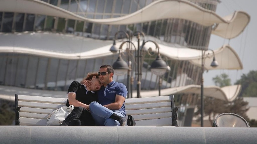A couple sit near the National  Gymnastics arena, on the eve of the opening of the 2015 European Games, in Baku, Azerbaijan, Thursday, June 11, 2015. (AP Photo/Dmitry Lovetsky)