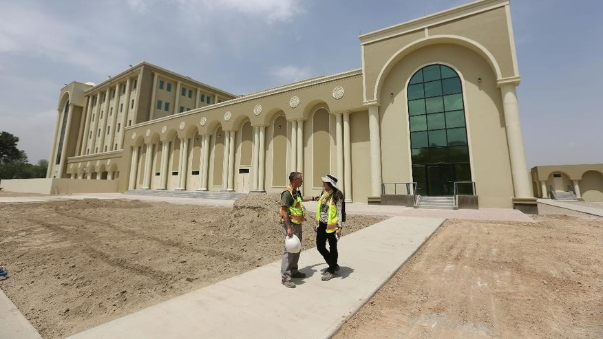 "In this Wednesday, May 6, 2015, photo, U.S. engineers chat in front of  Afghanistan's new Defense Ministry building, in Kabul, Afghanistan. In Kabul, they call it the ""mini Pentagon,"" the new headquarters for Afghanistan's Ministry of Defense _ a gleaming, white marble building in the center of the capital built with U.S. funds and due to be handed over to the Afghan government this month. (AP Photo/Rahmat Gul)"
