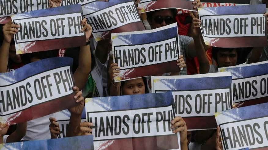 Protesters carry placards as they march in a Philippines Independence Day rally toward the Chinese Consulate in the financial district of Makati city east of Manila, Philippines, Friday, June 12, 2015. The protesters condemned the recent reclamation of land by China in the disputed Spratlys group of islands on the South China Sea. (AP Photo/Bullit Marquez)