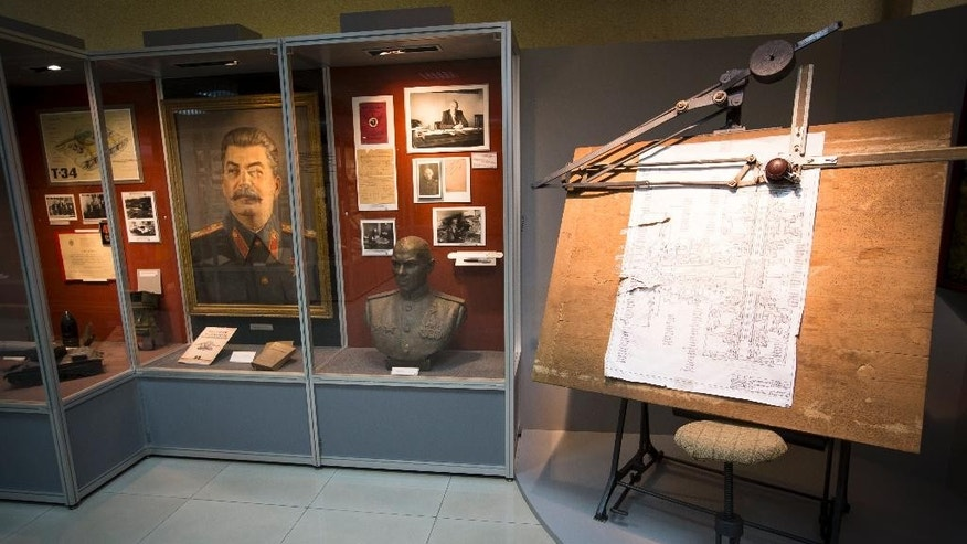 In this photo taken on Friday, May  29, 2015, a portrait of Soviet dictator Josef Stalin, left, and a drawing board, right, are displayed at a museum of the UralVagonZavod factory in the Ural's city of Nizhniy Tagil, Russia. The giant UralVagonZavod factory in the Urals Mountains, one of the biggest industrial plants in the world, has been the main manufacturer of tanks for the Soviet and then Russian military since World War II. (AP Photo/Alexander Zemlianichenko)