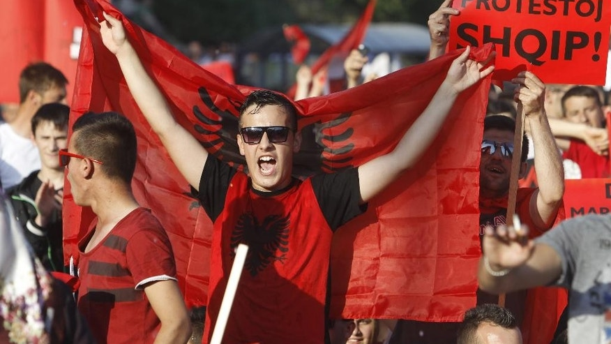 "Ethnic Albanians wave Albanian flags and carry banners reading ""Albanian protest"" while marching through a street in Skopje, Macedonia, on Saturday, June 13, 2015. About 2,000 ethnic Albanians marched peacefully Saturday afternoon protesting conservative government policies toward the largest ethnic minority in Macedonia, a tiny Balkan country shaken with one of the deepest political crises since it declared independence from former Yugoslavia in 1991. (AP Photo/Boris Grdanoski)"