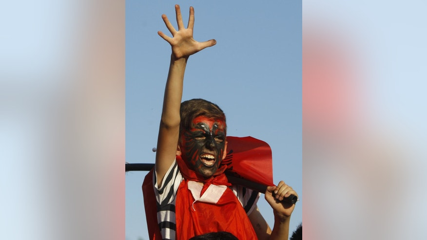 A boy with his face painted in the colours of the Albanian flag, gestures, during a protest in Skopje, Macedonia, Saturday, June 13, 2015. About 2,000 ethnic Albanians marched peacefully Saturday afternoon protesting conservative government policies toward the largest ethnic minority in Macedonia, a tiny Balkan country shaken with one of the deepest political crises since it declared independence from former Yugoslavia in 1991. (AP Photo/Boris Grdanoski)