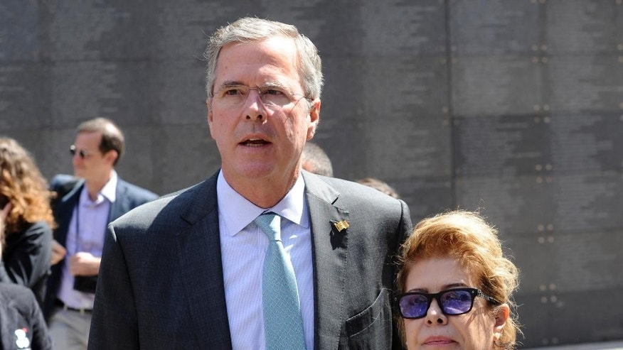 In this June 11, 2015, photo, former Florida Gov. Jeb Bush with wife Columba stand in front of the Wall of Memory at the Warsaw Uprising 1944 museum in Warsaw, Poland. Bush strolled the halls of the Polish parliament. He praised Germany's economic boom since the fall of the Berlin Wall. And he visited Estonia, a once-bleak Soviet state that now has a growing, free-market economy. If he was trying to stoke memories of his father and his legacy as president, Bush appears to have largely succeeded.  (AP Photo/Alik Keplicz)
