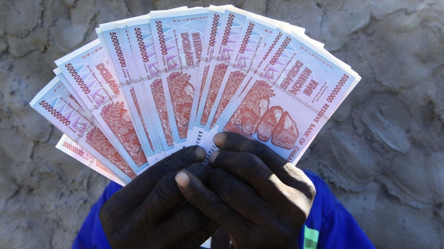 June 12, 2015: A man holds a handful of 5 Billion Zimbabwean dollar notes, in Harare.