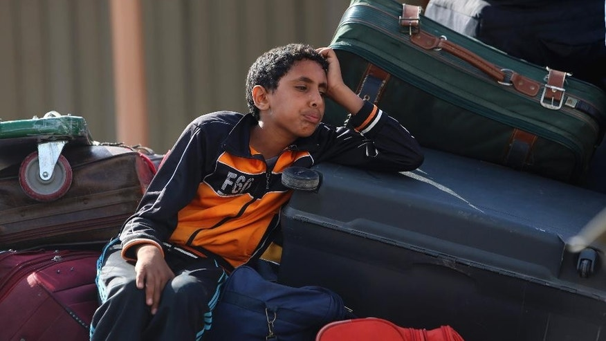 A Palestinian youth sits with his family's luggage as they wait to cross to the Egyptian side of the Rafah border crossing, in the southern Gaza Strip, Saturday, June 13, 2015. Egypt has opened its borders with the Gaza Strip for the first time in months on Saturday and will operate for three days, allowing Palestinians to travel in both directions. Maher Abu Sabha, head of Gaza's crossing, says 15,000 people have applied to exit. Rafah is Gaza's only gateway to the outside world with no Israeli control. (AP Photo/Adel Hana)