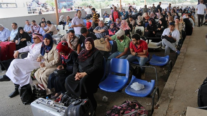 Palestinians wait to cross the border to the Egyptian side of the Rafah border crossing, in Rafah, in the southern Gaza Strip, Saturday, June 13, 2015. Egypt has opened its borders with the Gaza Strip for the first time in months on Saturday and will operate for three days, allowing Palestinians to travel in both directions. Maher Abu Sabha, head of Gaza's crossing, says 15,000 people have applied to exit. Rafah is Gaza's only gateway to the outside world with no Israeli control. (AP Photo/Adel Hana)