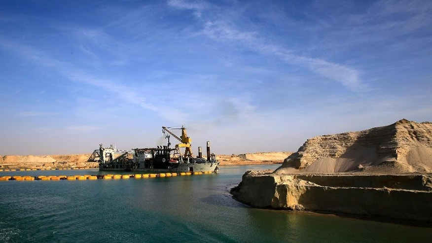 FILE - In this Feb. 4, 2015 file photo, a dredger floats on a new section of the Suez canal during a media tour in Ismailia, Egypt. The Suez Canal Authority said Saturday, June 13, 2015, that work on a parallel waterway to allow two-way traffic on the key trade route will be finished in time for a gala inauguration on Aug. 6. President Abdel-Fattah el-Sissi ordered the new waterway to be dug in a single year, saying that the urgency of Egypt's economic situation meant the project could not wait for an originally planned three-year timetable. (AP Photo/Hassan Ammar, File)