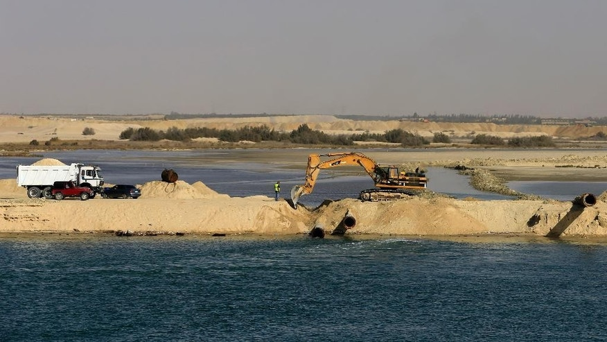 FILE - In this Feb. 4, 2015 file photo, bulldozers and trucks work on a new section of the Suez Canal during a media tour in Ismailia, Egypt. The Suez Canal Authority said Saturday, June 13, 2015, that work on a parallel waterway to allow two-way traffic on the key trade route will be finished in time for a gala inauguration on Aug. 6. President Abdel-Fattah el-Sissi ordered the new waterway to be dug in a single year, saying that the urgency of Egypt's economic situation meant the project could not wait for an originally planned three-year timetable. (AP Photo/Hassan Ammar, File)