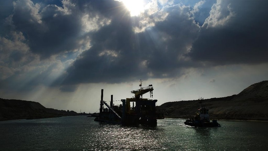 A dredger works on a new section of the Suez canal during a media tour in Ismailia, Egypt, Saturday, June 13, 2015. The Suez Canal Authority said Saturday that work on a parallel waterway to allow two-way traffic on the key trade route will be finished in time for a gala inauguration on Aug. 6. President Abdel-Fattah el-Sissi ordered the new waterway to be dug in a single year, saying that the urgency of Egypt's economic situation meant the project could not wait for an originally planned three-year timetable. (AP Photo/Hassan Ammar)