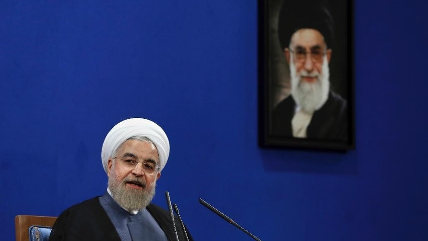 "Iranian President Hassan Rouhani speaks during a press conference on the second anniversary of his election, in Tehran, Iran, Saturday, June 13, 2015. Rouhani said a final nuclear deal is ""within reach"" as Iran and world powers face a June 30 deadline for an agreement. Rouhani said Iran will allow inspections of its nuclear facilities but vowed that the Islamic republic won't allow its state ""secrets"" to be jeopardized under the cover of international inspections. A picture of the supreme leader Ayatollah Ali Khamenei hangs on the wall. (AP Photo/Ebrahim Noroozi)"