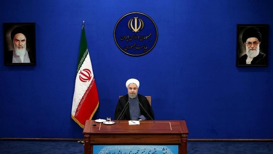 "Iranian President Hassan Rouhani gives a press conference on the second anniversary of his election, in Tehran, Iran, Saturday, June 13, 2015. Rouhani said a final nuclear deal is ""within reach"" as Iran and world powers face a June 30 deadline for an agreement. Rouhani said Iran will allow inspections of its nuclear facilities but vowed that the Islamic republic won't allow its state ""secrets"" to be jeopardized under the cover of international inspections. Pictures of the late Iranian revolutionary founder Ayatollah Khomeini, left, and supreme leader Ayatollah Ali Khamenei, right, hang on the wall. (AP Photo/Ebrahim Noroozi)"