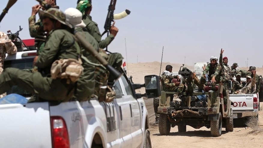 In this Friday, June 12, 2015 photo, fighters from the Shiite Badr Brigades militia patrol at the front line, in Kessarrat, (70 kilometers) northwest of Baghdad, Iraq. Despite concerns over heightened sectarian strife, Shiite militiamen continue to pour into Iraq's Anbar province with the hope of recapturing the city of Fallujah from the Islamic State group. As the U.S. prepares to send an additional 450 trainers to Iraq, the Iranian-backed militias say that coalition assistance only hurts their efforts, contradicting statements by the Iraqi government that more international support is needed. (AP Photo/Hadi Mizban)