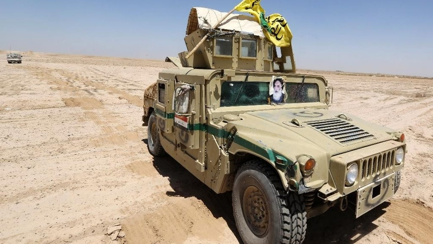 In this Friday, June 12, 2015 photo, an Iraqi army armored vehicle with a poster of Iranian Shiite spiritual leader Grand Ayatollah Ali al-Sistani patrol at the front line, in Kessarrat, (70 kilometers) northwest of Baghdad, Iraq. Despite concerns over heightened sectarian strife, Shiite militiamen continue to pour into Iraq's Anbar province with the hope of recapturing the city of Fallujah from the Islamic State group. As the U.S. prepares to send an additional 450 trainers to Iraq, the Iranian-backed militias say that coalition assistance only hurts their efforts, contradicting statements by the Iraqi government that more international support is needed. (AP Photo/Hadi Mizban)