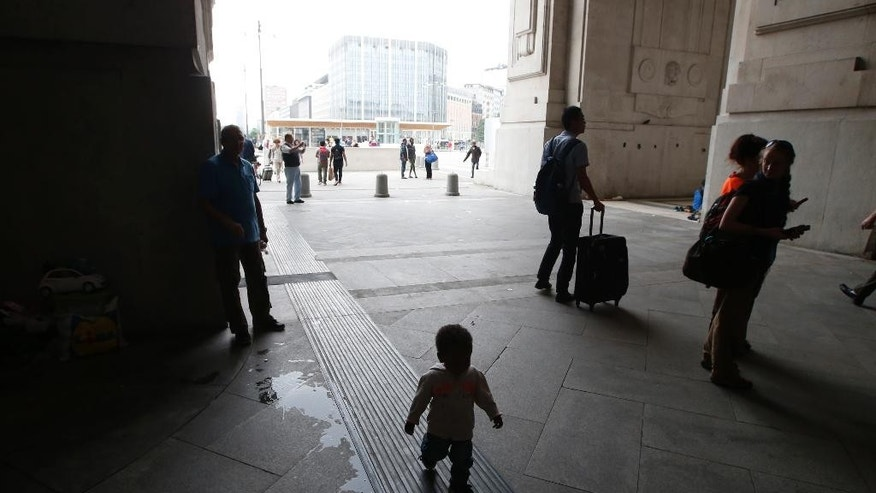 A child walks at Milan's main train station, Italy, Saturday, June 13, 2015. Milan city officials have appealed for help in managing the huge flow of migrants arriving from southern Italy after rescue at sea, as increasing numbers are unable to find beds and are sleeping in the train station. (AP Photo/Luca Bruno)