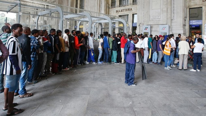Migrants queue to receive clothes at Milan's main train station, Italy, Saturday, June 13, 2015. Milan city officials have appealed for help in managing the huge flow of migrants arriving from southern Italy after rescue at sea, as increasing numbers are unable to find beds and are sleeping in the train station. (AP Photo/Luca Bruno)