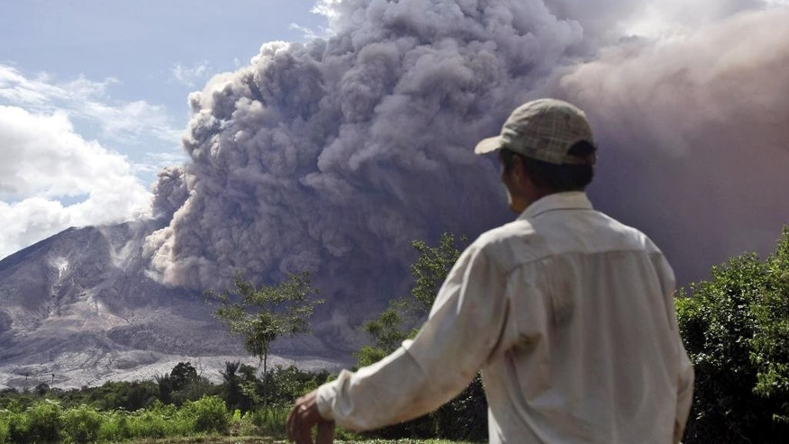 A farmer watches as Mount Sinabung releases pyroclastic flows in Tiga Pancur, North Sumatra, Indonesia, Saturday, June 13, 2015. The volcano, which was put on it highest alert level last week, has sporadically erupted since 2010 after being dormant for 400 years. (AP Photo/Binsar Bakkara)