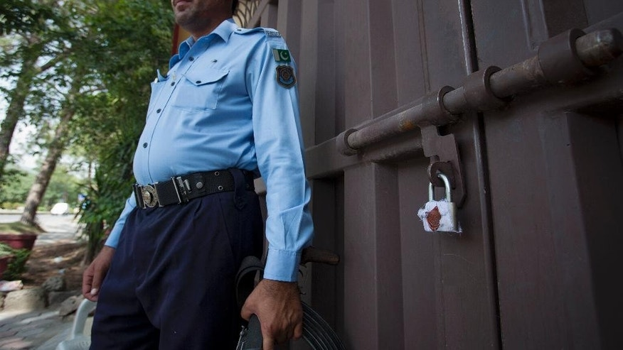 A Pakistani police officer stands guard outside a sealed 'Save the Children' office in Islamabad, Pakistan, Friday, June 12, 2015. The Pakistani government shut down the offices of the international aid group for violating its charter, the country's interior minister and officials said Friday. (AP Photo/B.K. Bangash)