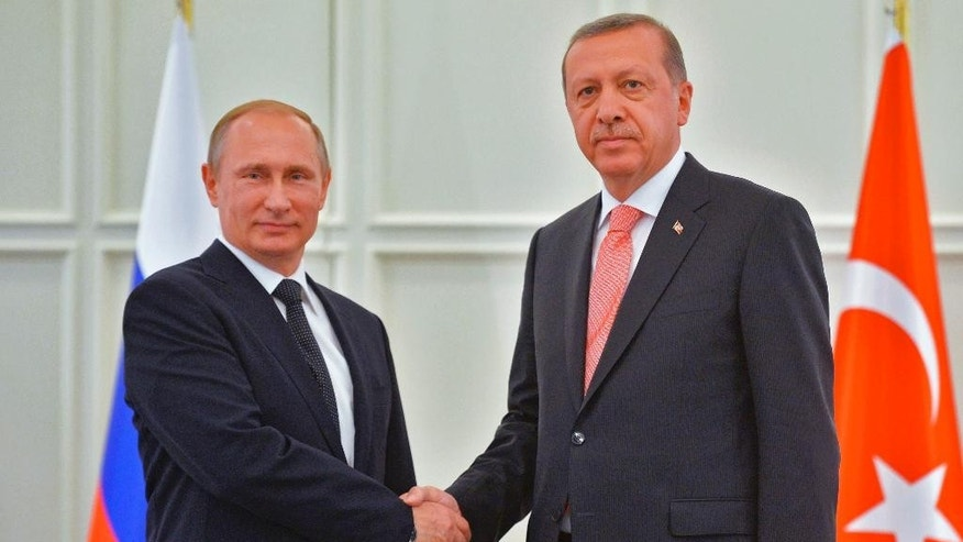 Russian President Vladimir Putin, left, and Turkish President Recep Tayyip Erdogan shake hands during their meeting in Baku, Azerbaijan, Saturday, June 13, 2015. Russian President Vladimir Putin attended the opening ceremony of the the 2015 European Games in Baku on Friday.  (Alexei Druzhinin/RIA-Novosti, Kremlin Pool Photo via AP)